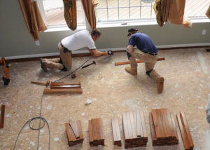 Two men working on a house's living room